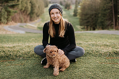 Smiling woman with poodle sitting on grassy land in park - p300m2203014 by Sara Monika
