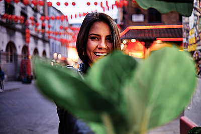 Happy young woman in front of plant in city - p300m2273690 by Angel Santana Garcia