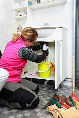 Female plumber repairing bathroom sink - p312m2262864 by Phia Bergdahl