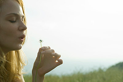 Young woman blowing dandelion seedhead - p6244219f by Laurence Mouton