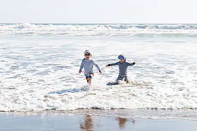 Two children playing in the surf - p756m2057695 by Bénédicte Lassalle