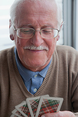 Senior man playing cards at home - p924m1174862 by REB Images
