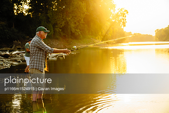 Side view of friends fishing while standing in lake during sunset - p1166m1524915 by Cavan Images