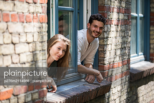 Young couple looks out the window - p276m2114986 by plainpicture