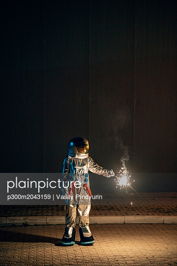 Spaceman standing on a road at night holding sparkler - p300m2043159 von Vasily Pindyurin