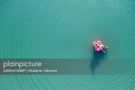 Young man with flamingo pool float on the lake - p300m2143907 by Ekaterina Yakunina