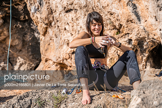 Smiling woman having a break from climbing at rock face - p300m2166801 by Javier De La Torre Sebastian