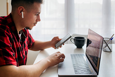 Male entrepreneur with in-ear headphones holding smart phone while working on laptop at home office - p300m2267749 by Marco Govel