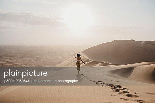 Namibia, Namib, back view of woman standing on desert dune looking at view - p300m2080841 by letizia haessig photography