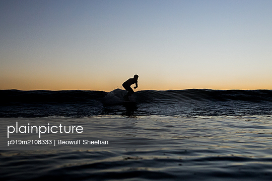 Surfer at sunset - p919m2108333 by Beowulf Sheehan