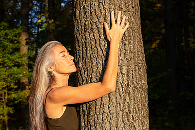 Woman with eyes closed hugging tree at park - p300m2240429 by Christina Falkenberg
