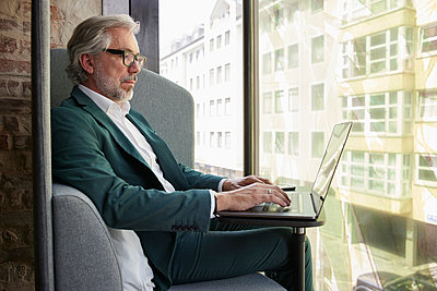 Mature male professional working using laptop while sitting on sofa by glass window in office - p300m2300419 by Rainer Berg
