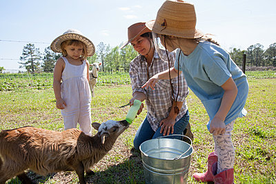 Mother and two children on farm, bottle feeding young goat - p924m1495001 by Kinzie Riehm