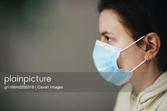 Young woman on the white background wearing a face mask - p1166m2255318 by Cavan Images