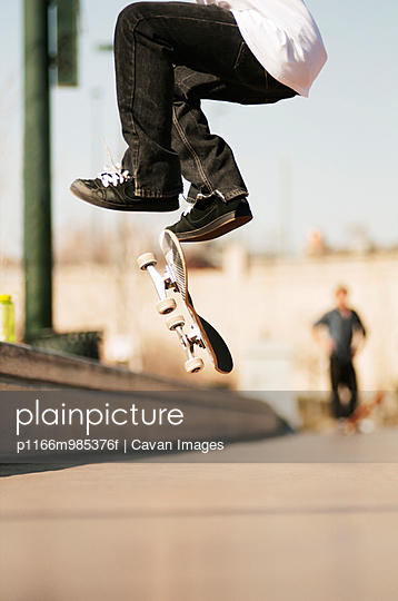 Surface level of man jumping with skateboard on footpath - p1166m985376f by Cavan Images