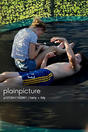 Junge und Mädchen chillen auf dem Trampolin - p1212m1152961 von harry + lidy