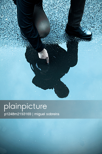 Man crouching at and touching puddle - p1248m2193169 by miguel sobreira