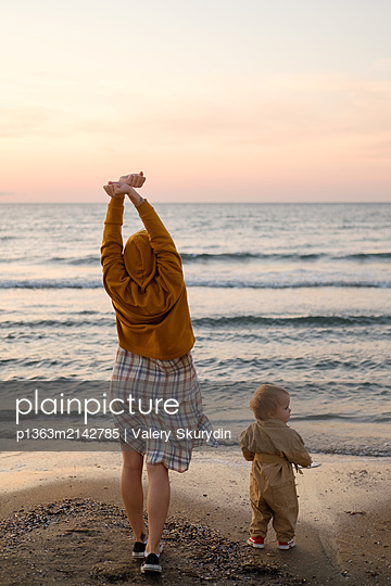 Woman with baby stretches on beach  - p1363m2142785 by Valery Skurydin