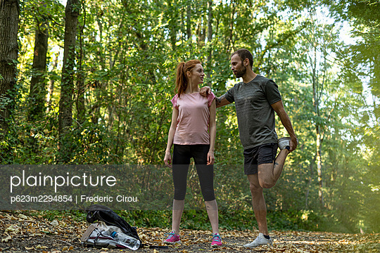 Young couple exercising on track in forest - p623m2294854 by Frederic Cirou