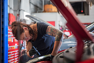 Female tattooed mechanic examining car engine in auto repair shop - p1166m2105704 by Cavan Images