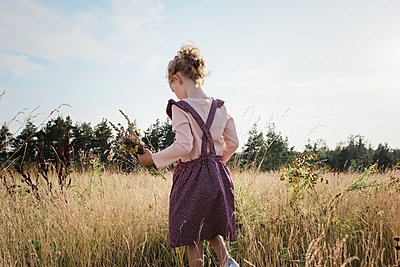 rear view of young girl walking through a meadow with wildflowers - p1166m2137960 by Cavan Images
