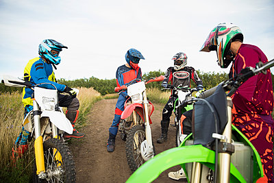 Male friends on motorbikes talking on rural dirt road - p1192m1500161 by Hero Images