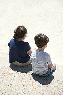 Boy and girl sitting on beach promenade - p1248m1538601 by miguel sobreira