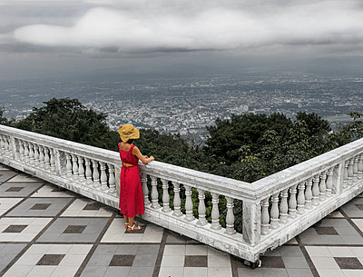 Woman in red dress looking out over city - p1445m2122710 by Eugenia Kyriakopoulou