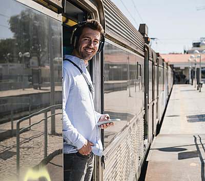 Smiling young man with headphones and smartphone standing in train door - p300m2155841 by Uwe Umstätter