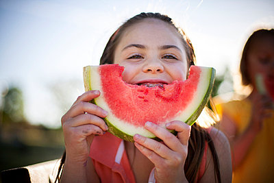 Smiling girl eating watermelon - p429m768852f by Jamie Kingham
