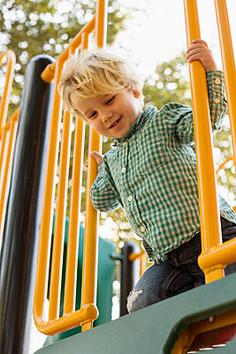 Caucasian boy on play structure in playground - p555m1410880 by Roberto Westbrook