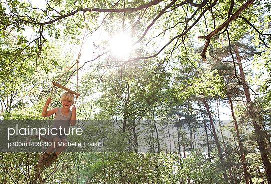 Happy boy on swing in forest