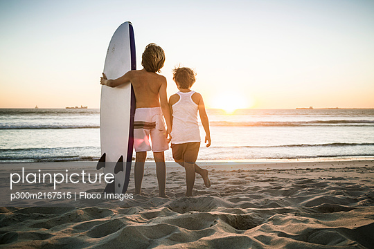 Rear view of two boys with surfboard standing on the beach at sunset - p300m2167515 by Floco Images
