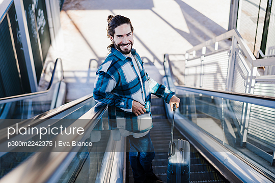 Man smiling while standing with luggage on escalator - p300m2242375 by Eva Blanco