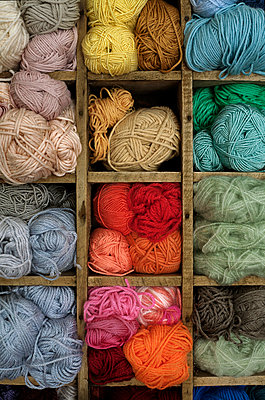 Balls of yarn stored in an old wooden bottle crate - p1028m1051630 by Jean Marmeisse