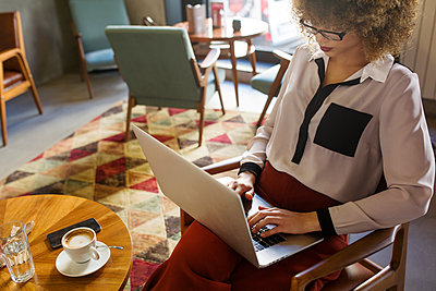 Businesswoman using laptop in hotel lobby - p1166m1151367 by Cavan Images
