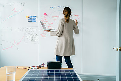 Rear view of businesswoman writing on whiteboard while working over solar panels in office - p1166m1474622 by Cavan Images