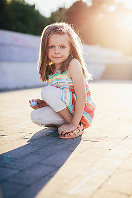 Portrait of girl holding chalk while crouching on street - p1166m2011631 by Cavan Images