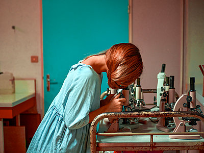 Young woman looking through a microscope - p1413m2278745 by Pupa Neumann