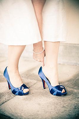 Woman putting on blue shoes - p1687m2284349 by Katja Kircher