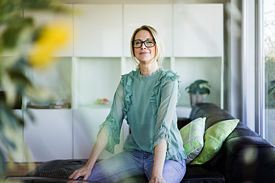 Portrait of content businesswoman sitting on couch - p300m1586963 by Robijn Page