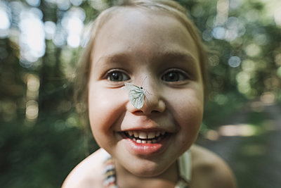 Portrait of smiling little girl with butterfly on her nose - p300m2029716 by Katharina Mikhrin