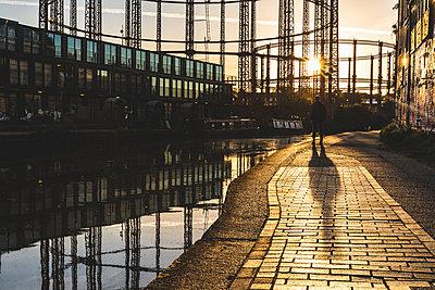 United Kingdom, England, London, man standing at Regent's canal against the evening sun - p300m2070553 von William Perugini