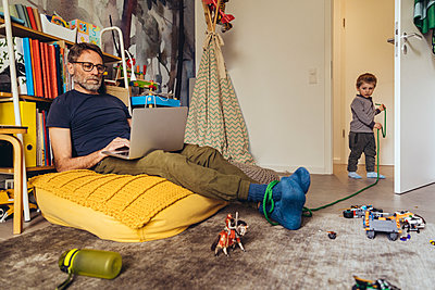 Son tying his father working on laptop in children's room - p300m2180659 by Mareen Fischinger