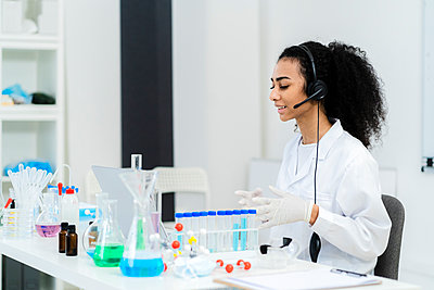 Young female researcher talking on video call through laptop in laboratory - p300m2265598 by Giorgio Fochesato