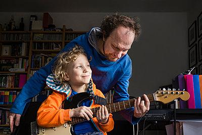 Man teaching guitar to smiling son looking away at home - p300m2277150 by Irina Heß