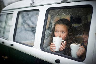 Girls drinking hot chocolate inside camper van - p429m2036643 by Peter Mason