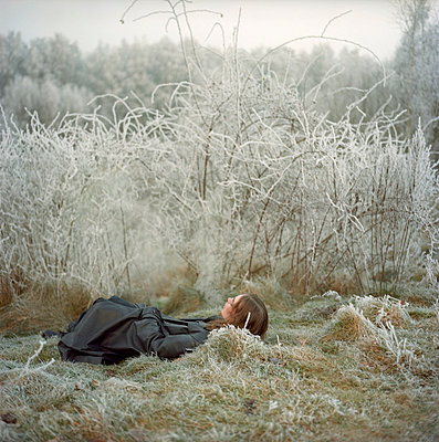 Woman lying on frozen ground - p9060039 by Wassily Zittel
