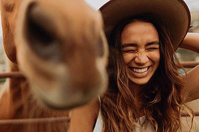 Young woman in felt hat laughing next to horse, Jalama, California, USA - p924m2068159 by Peter Amend