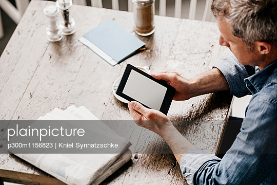 Mature man sitting in cafe with newspaper and digital tablet - p300m1156823 by Kniel Synnatzschke